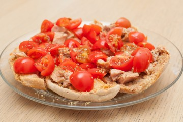 Dried bread called freselle with tuna and tomatoes on wooden table