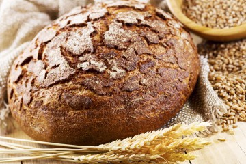 fresh bread with wheat ears on wooden table